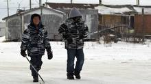 Two boys walk past substandard housing on their way to play hockey in Attawapiskat on Dec. 17, 2011 (Frank Gunn/Frank Gunn/The Canadian Press)