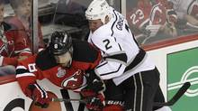 New Jersey Devils' Dainius Zubrus, left, and Los Angeles Kings' Matt Greene struggle to reach the puck during the first period of Game 1 of the NHL hockey Stanley Cup finals Wednesday, May 30, 2012, in Newark, N.J. (Associated Press)