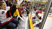 Fans react to a hit in the corner during the first period of the game between the Ottawa Senators and the Buffalo Sabres. (Peter Power/Peter Power/The Globe and Mail)