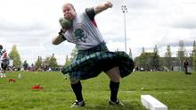 A competitor tosses a largish rock during the 147th Victoria Highland Games and Celtic Festival in Victoria, B.C., in May 2010. (The Globe and Mail)
