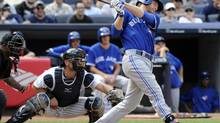 Toronto Blue Jay' Dan Johnson, right, hits a three-run home run as New York Yankees catcher Francisco Cervelli, left, looks on during the ninth inning of a baseball game on Saturday, July 26, 2014, at Yankee Stadium in New York. (Bill Kostroun/Associated Press)