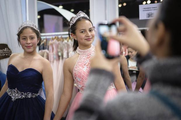 (L-R) Vanessa Jardon and Julieta Leon, fourteen year old best friends from Mexico City have their photo taken while trying on dresses at the Picchelina stand at 15 Fest, a quinceañera convention in Mexico City, Mexico. Alicia Vera/The Globe and Mail