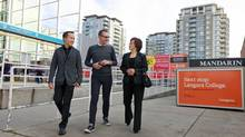 Bob Rennie, centre, walks with sales associates Diana Wang and Derek Kai beside the site for the Mandarin Residences. (Jeff Vinnick/The Globe and Mail)