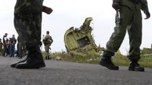 Armed pro-Russian separatists stand guard as monitors from the Organization for Security and Co-operation in Europe and members of a Malaysian air crash investigations team inspect the crash site of Malaysia Airlines Flight 17 near the village of Grabovo, Donetsk region, on July 22, 2014. (MAXIM ZMEYEV/REUTERS)