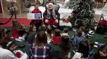 Children and parents gather around Santa Claus at the Santa Experience at Sherway Gardens in Etobicoke. (Moe Doiron/The Globe and Mail)