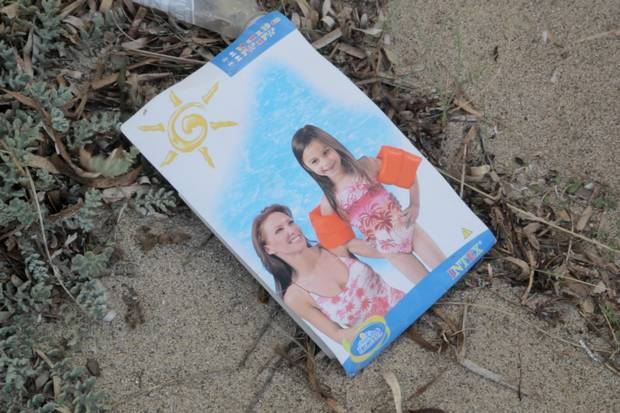 An abandoned package for a child's inflatable arm rings lies on Dikili beach, north of Izmir, Turkey.