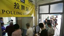 People queue up at a polling station on the last day to vote for an unofficial referendum on democratic reform in Hong Kong on June 29, 2014. (KIN CHEUNG/ASSOCIATED PRESS)