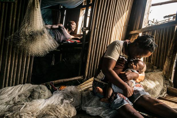 Christiane Djengue sits on fishing nets and plays with her son while her husband rest in the bedroom. She has given birth to 10 children in 19 years, but suffered complications in most of them.