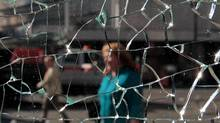 A woman walks past a shattered window at a commuter train station in Vancouver, B.C., on Thursday June 16, 2011, after a riot following the Vancouver Canucks loss to the Boston Bruins in the NHL's Stanley Cup Final Wednesday night. (DARRYL DYCK/THE CANADIAN PRESS)