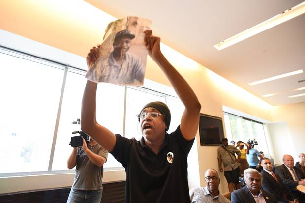 Holding a photo of Andrew Loku, Cecil Peter speaks out against carding during a public consultation on street checks in Toronto.