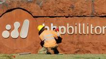A man mends a sign at the entrance to BHP Billiton's iron ore loading facility in Port Hedland, about 1,600 km (994 miles) north of Perth in this May 30, 2008 file photo. (TIM WIMBORNE/REUTERS)