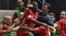 Canada's players celebrate after Olivier Occean, partially covered by teammates, scored against Cuba during a 2014 World Cup qualifying soccer game in Havana, Cuba, Friday June 8, 2012. (Associated Press)