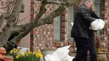 A B.C. Coroner carries the body of a newborn baby after it was found dead in a plastic bag between two homes in Vancouver, B.C., on April 2, 2009. (Darryl Dyck/The Canadian Press)