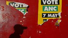 The shadow of a man falls next to African National Congress (ANC) posters on a wall on the voting day in Du Noon township near Cape Town May 7, 2014. (STRINGER/REUTERS)