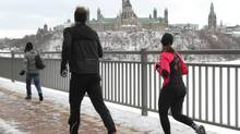 With Parliament Hill in the background, joggers runs across the Interprovincial bridge between Ottawa and Gatineau. (FRED CHARTRAND/THE CANADIAN PRESS)
