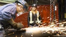 Heather Reid, safety co-ordinator for Supreme Steel, talks to one of the shop workers in a fabrication plant in Edmonton. (Ian Jackson for The Globe and Mail)