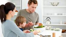 Dad serving salad to his family for lunch. (Thinkstock)