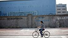 A woman rides her bicycle in front of a closed factory in Wenzhou, China, Oct. 17, 2011. (CARLOS BARRIA/REUTERS/CARLOS BARRIA/REUTERS)