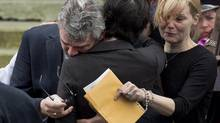 Glen Canning, left, father of Rehtaeh Parsons, is comforted outside St. Mark's Anglican Church at Rehtaeh's funeral in Halifax on Saturday, April 13, 2013. (Andrew Vaughan/THE CANADIAN PRESS)