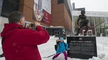A man takes a photograph of a child outside the Bell Centre in Montreal, Sunday, January 6, 2013. photo Graham Hughes for The Globe and Mail. (Graham Hughes/The Globe and Mail)
