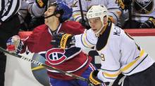 Montreal Canadiens' Aaron Palushaj takes a hit from Buffalo Sabres' Cody McCormick during second period NHL hockey action Monday, November 14, 2011 in Montreal. (Paul Chiasson/THE CANADIAN PRESS)