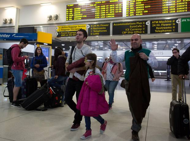 Fuad Sharef Suleman, right, and two of his children arrive in New York on Sunday. The Iraqi family was previously prevented from boarding a plane to the United States following U.S. President Donald Trump's executive order to temporarily bar travellers from seven countries, including Iraq.