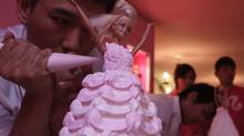 A man decorates a Barbie doll cake during a media preview of the Barbie Café in Taipei Jan. 30, 2013. (PICHI CHUANG/REUTERS)