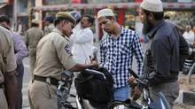 An Indian police officer checks the bags of motorists in Hyderabad. (Mahesh Kumar A/AP)
