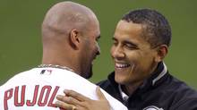 U.S. President Barack Obama embraces St. Louis Cardinals baseball player Albert Pujols after Obama threw out the ceremonial first pitch prior to the start of Major League Baseball's All-Star game in St. Louis, July 14, 2009. (POOL)