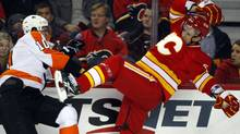Philadelphia Flyers' Brayden Schenn, left, checks Calgary Flames' Cory Sarich along the boards during second period NHL hockey action in Calgary, Alta., Saturday, Feb. 25, 2012.THE CANADIAN PRESS/Jeff McIntosh (Jeff McIntosh/CP)
