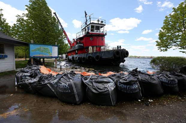 Radium Yellowknife loads large sandbags on the boat on Ward's Island to be moved to another spot where it is needed.