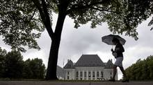 A pedestrian walks past the Supreme Court of Canada in Ottawa on Thursday June 10, 2010. The Supreme Court of Canada has upheld a defendant's right to have an automatic publication ban on evidence at their bail hearing. (Sean Kilpatrick/The Canadian Press/Sean Kilpatrick/The Canadian Press)