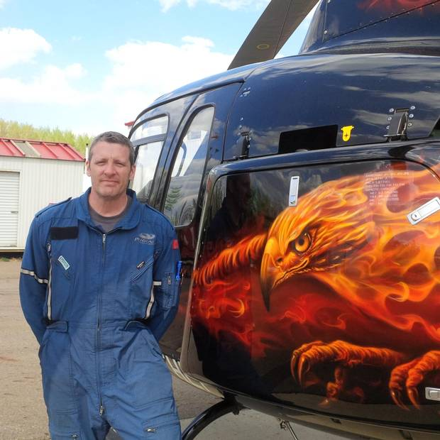 Ken Saumure, a pilot with Phoenix Heli-Flight stands beside a helicopter after dousing a hotspot near the facility in Fort McMurray.