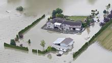 A house is surrounded by water after the Fraser River burst its banks in Chilliwack, British Columbia June 24, 2012. (ANDY CLARK/THE CANADIAN PRESS)