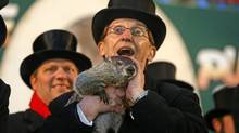 Punxsutawney Phil is held by Ron Ploucha after emerging from his burrow Feb. 2 on Gobblers Knob in Punxsutawney, Pa., to see his shadow and forecast six more weeks of winter weather. The prediction this year fell on the same day as Super Bowl Sunday. (Gene J. Puskar/Associated Press)