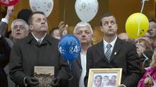 Patrick Desautels, right, father of Loreilie, Loic and Anais, looks up as balloons are released following their funeral in Acton Vale, Que., Saturday, December 8, 2012. (Graham Hughes/The Canadian Press)