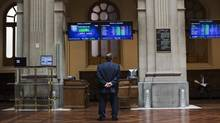 A trader looks at electronic boards at Madrid's stock exchange on June 29, 2012. The euro jumped nearly 2 per cent, oil prices soared and world stocks rallied on Friday after euro zone leaders agreed on measures to cut soaring borrowing costs in Italy and Spain, in addition to directly recapitalizing regional banks. (Susana Vera/Reuters)