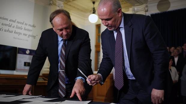B.C. NDP leader John Horgan and B.C. Green party leader Andrew Weaver sign an agreement on creating a stable minority government during a press conference in the Hall of Honour at Legislature in Victoria, B.C., on Tuesday, May 30, 2017.