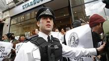 A police officer controls demonstrators outside a Starbucks coffee shop in central London in December. (LUKE MACGREGOR/REUTERS)