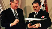 Airlines' president Kevin Benson gives British Columbia Premier Glen Clark (R) a model of a Canadian Airlines Boeing 747 as a gift, November 29, 1996 in Vancouver after the Premier announced his government would be giving the cash strapped airline financial support. (Jeff Vinnick/ Reuters/Jeff Vinnick/ Reuters)