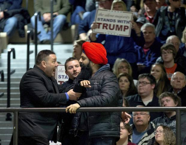 A protester, right, is removed after interrupting then-Republican presidential candidate Donald Trump as he speaks at a rally at Muscatine High School in Muscatine, Iowa, on Jan. 24, 2016.