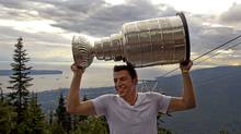 Boston Bruins Milan Lucic holds up the NHL Stanley Cup atop Grouse Mountain in North Vancouver, British Columbia Aug. 14, 2011. (ANDY CLARK/REUTERS)