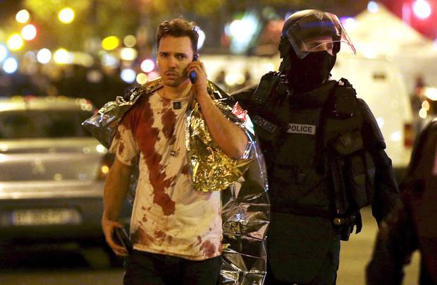 A French policeman assists a blood-covered victim near the Bataclan concert hall following attacks in Paris, Nov. 14, 2015.
