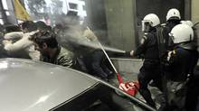 Riot police spray tear gas at protesters at the Greek Ministry of Employment in Athens, where a meeting was taking place with the EU's top financial official, Olli Rehn. (Aris Messinis/AFP/Getty Images)