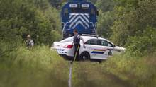 RCMP officers guard one of five locomotives on July 9, 2013, about a kilometre away from the crash site in Lac-Mégantic, Que. Police have confirmed that the rail cars are being treated as a crime scene. (MOE DOIRON/THE GLOBE AND MAIL)