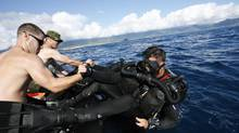 Members of the Canadian Navy's Fleet Diving Unit (Pacific), Leading Seaman Barry MacLeod (L) helps his colleague Leading Seaman Josh Adams into the water to perform an underwater sonar exercise looking for mines during the multi-lateral RIMPAC (Rim of the Pacific) military exercise in Kaneohe Bay in Kaneohe, Hawaii, July 14, 2010. (HUGH GENTRY/REUTERS)