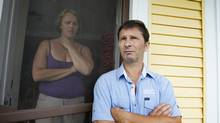Richard Bolduc and his wife, Johanne Orichefqui, stand in the doorway of their home speaking with some members of Quebec's health and social services ministry in Lac-Mégantic, Que., on July 9, 2013. The couple have been allowed to return to their home after a fatal train derailment and fire in the small town. (PETER POWER/THE GLOBE AND MAIL)