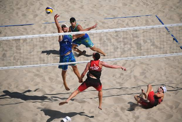 Bruno Oscar Schmidt (2) and Alison Cerutti of Brazil (1) and Josh Binstock (1) and Samuel Schachter of Canada (2) in action during the Men's Beach Volleyball preliminary round Pool A match on Day 1 of the Rio 2016 Olympic Games at the Beach Volleyball Arena on August 6, 2016 in Rio de Janeiro, Brazil.