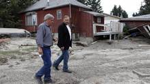 NDP leader Thomas Mulcair, right, tours a flood ravaged neighborhood with town councilor Jamie Kinghorn in High River, Alta., Thursday, July 4, 2013. (Jeff McIntosh/THE CANADIAN PRESS)
