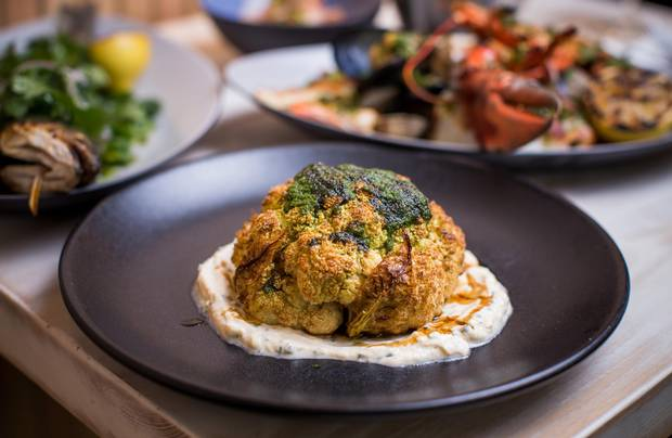 The cauliflower is served like a steak in one big, browned head drizzled with spicy green chermoula and tart pomegranate molasses.